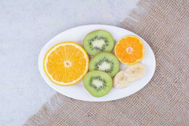 Un piatto bianco di frutta a fette su tela di sacco. foto di alta qualità