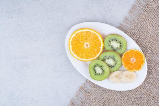Un piatto bianco di frutta a fette su tela di sacco.