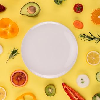 Белая тарелка в окружении овощей и фруктов