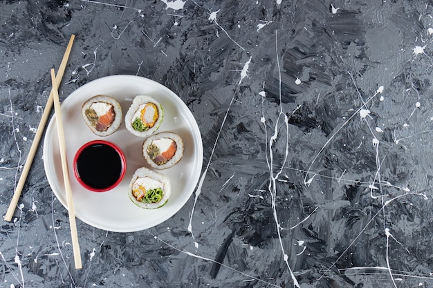 White plate of sushi rolls with tuna fish on marble background.