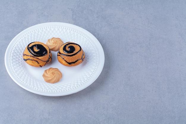 Un piatto bianco di deliziosi biscotti dolci con sciroppo di cioccolato.