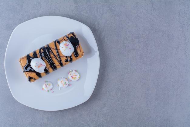 Un piatto bianco di rotolo delizioso dolce con sciroppo di cioccolato.