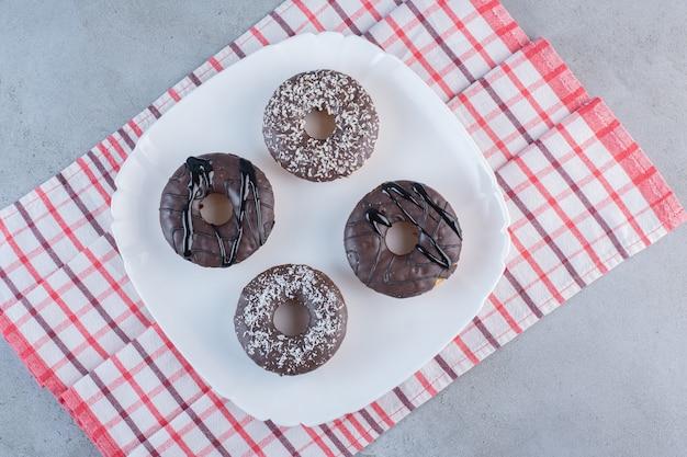 Piatto bianco di gustose ciambelle al cioccolato su pietra.
