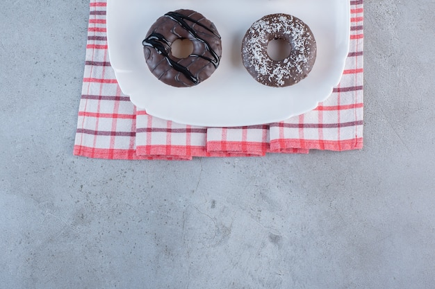 White plate of tasty chocolate donuts on stone.