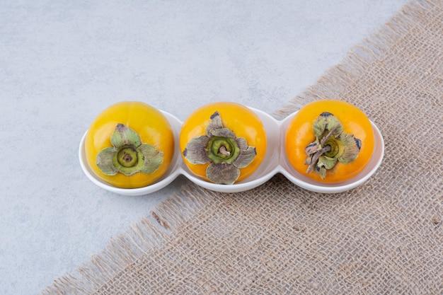 Un piatto bianco di tre cachi dolci su tela di sacco. foto di alta qualità