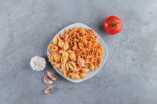 White plate of two various creamy pasta on stone background.