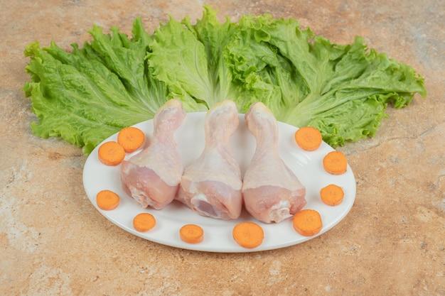 Un piatto bianco di cosce di pollo non preparate con lattuga e carote affettate