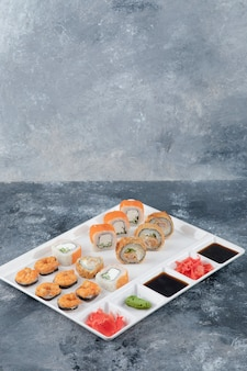 White plate of various delicious sushi rolls on marble background