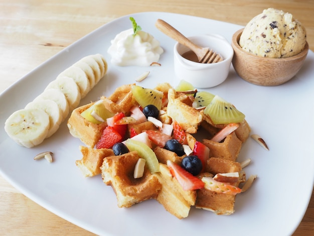 White plate of waffle with mixed fruit and ice cream on wooden table
