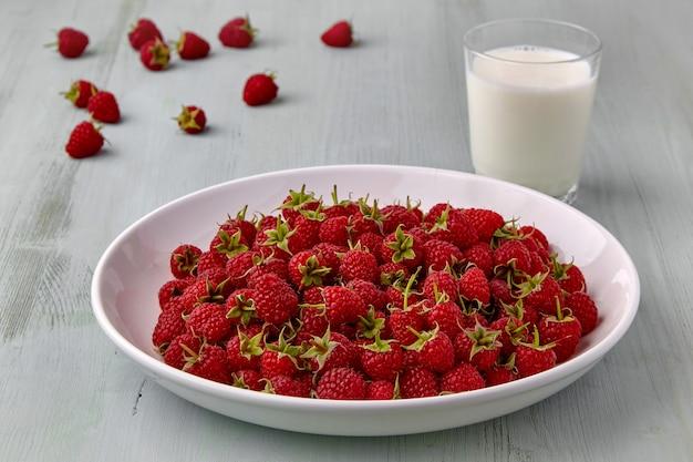 Белая тарелка со спелой красной малиной и стаканом молока