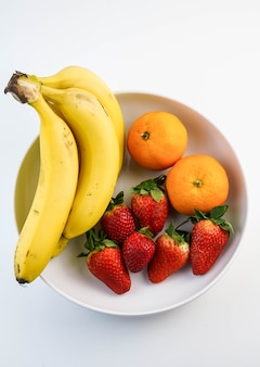 White plate with bananas oranges and strawberries
