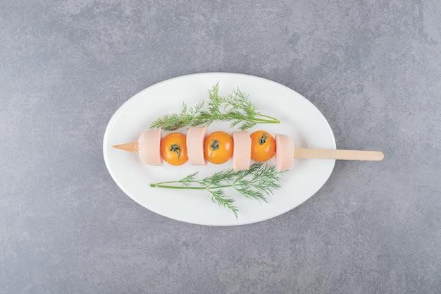 Un piatto bianco con salsiccia affettata bollita con pomodoro giallo ciliegia