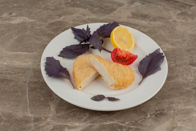 Белая тарелка с куриным наггетсом, лимоном, помидорами.