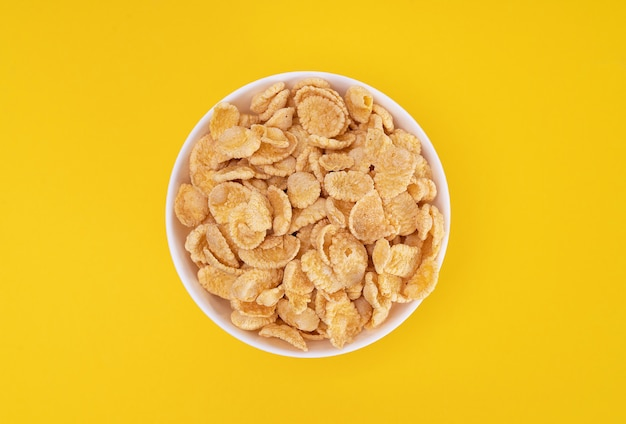 White plate with cornflakes for a delicious on yellow background