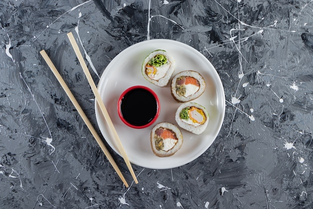 White plate with cucumber sushi roll on marble surface.