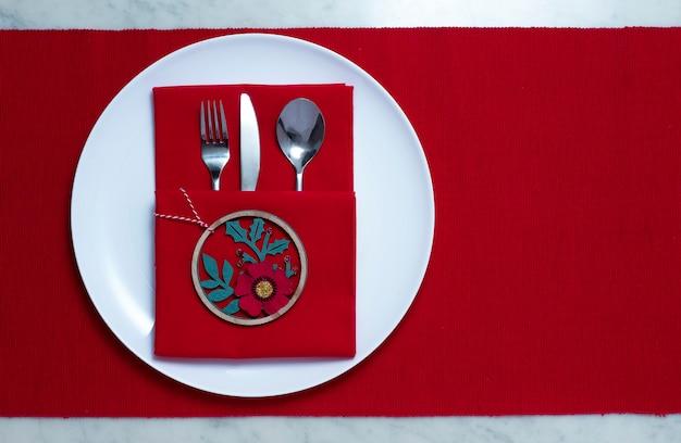 Белая тарелка со столовыми приборами, на красном столе, концепция рождественских настроек, горизонтальная, без людей. фото высокого качества