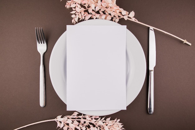 A white plate with cutlery and sprigs of decor on the table