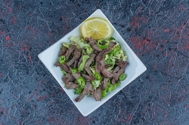 Un piatto bianco con carne ed erbe deliziose