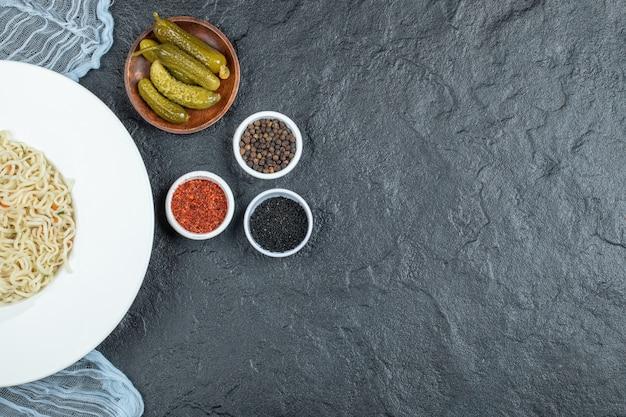 Un piatto bianco con deliziose tagliatelle e cetriolini sottaceto.
