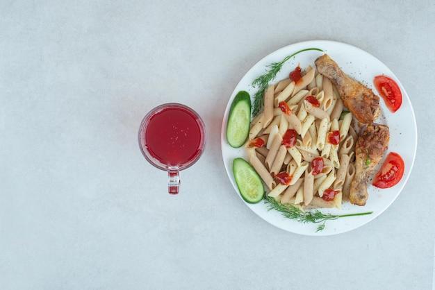 Un piatto bianco con pasta deliziosa e verdure a fette.
