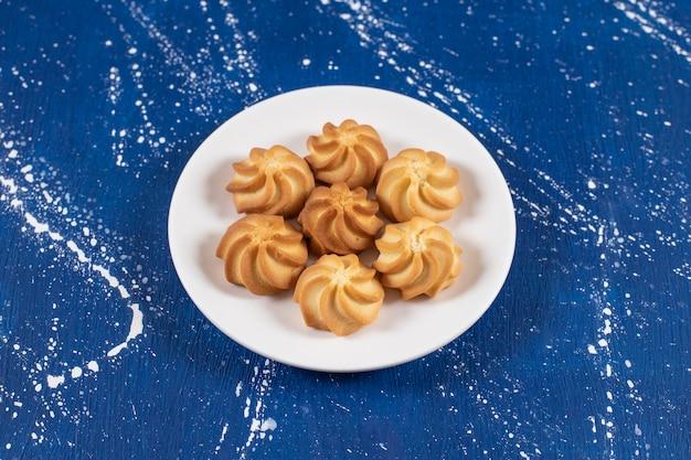블루 테이블에 맛있는 달콤한 쿠키와 화이트 플레이트.