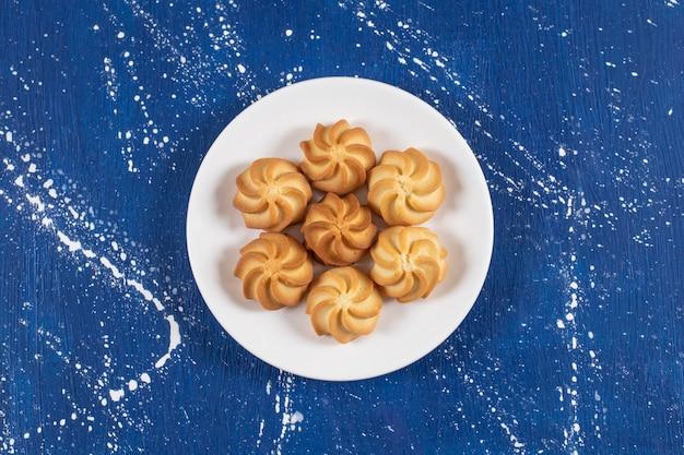 青においしい甘いクッキーが付いた白いプレート。