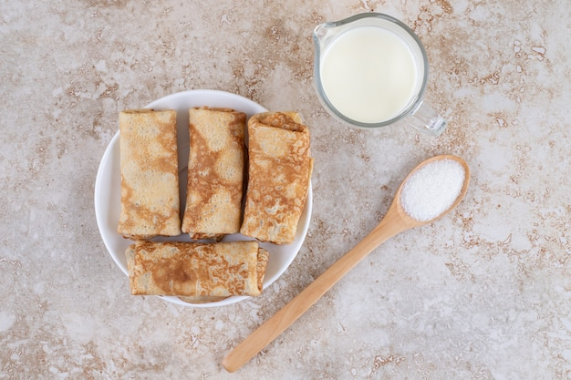 A white plate with delicious sweet crepes and a wooden spoon of sugar