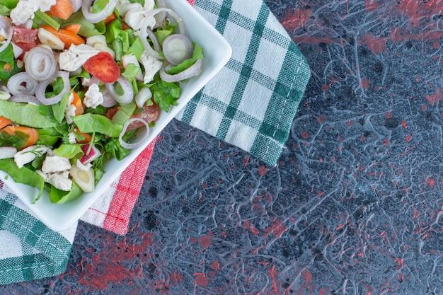 Un piatto bianco con una deliziosa insalata di verdure.