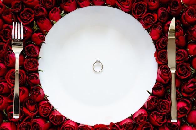 Белая тарелка с бриллиантовым кольцом на розах, обедая на день святого валентина концепции.