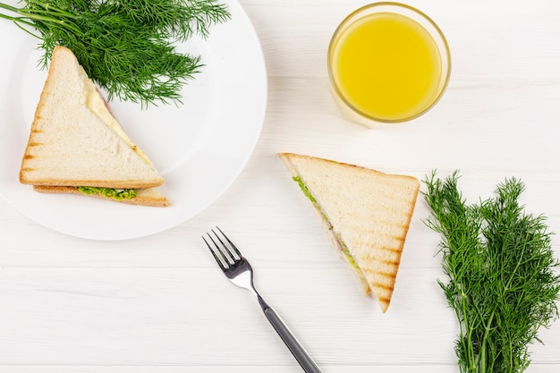 White plate with dill and sandwich on a white table