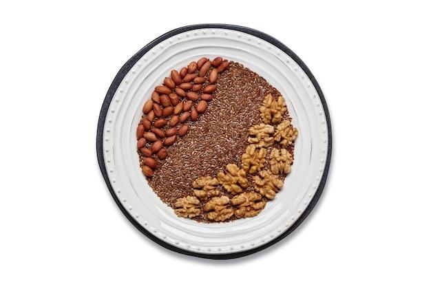 Белая тарелка с семенами льна, арахисом и грецкими орехами, изолированными на белом