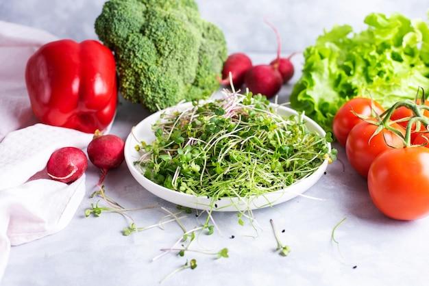 新鮮なマイクログリーンの白いプレートは、野菜、赤唐辛子、赤大根、ブロッコリー、グリーンサラダ、トマト、フラットレイの白いプレート上にあります