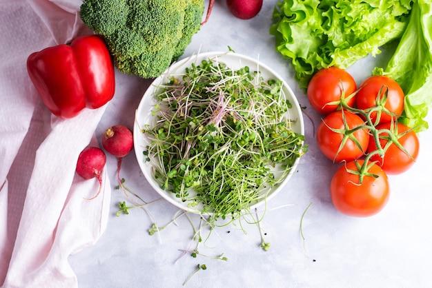 新鮮なマイクログリーンの白いプレートは、野菜、赤ピーマン、赤大根、ブロッコリー、レタス、トマト、フラットレイの白いプレート上にあります
