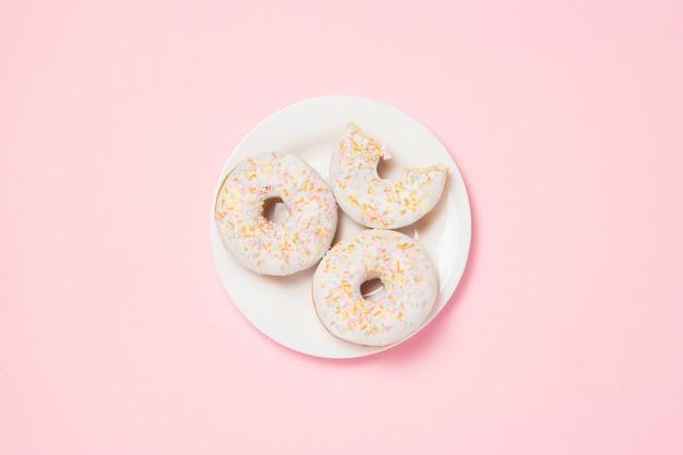 분홍색 배경에 신선한 맛있는 달콤한 도넛과 하얀 접시. 베이커리 개념, 신선한 파이, 맛있는 아침 식사, 패스트 푸드, 커피 숍. 평평한 평면도, 평면도
