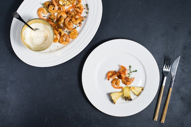 White plate with fried king prawns and pineapple slices.