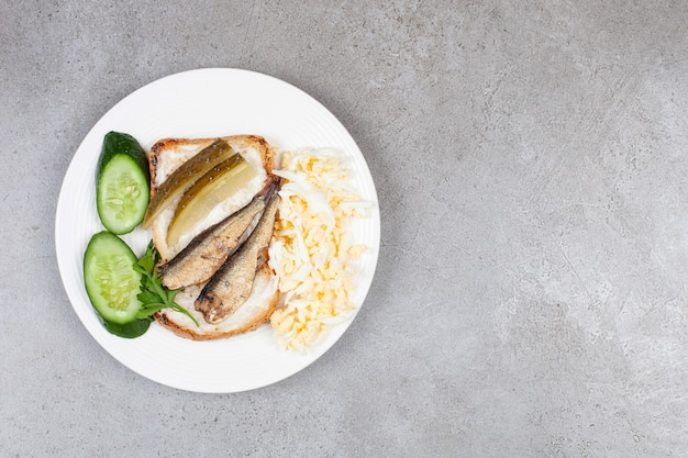 Un piatto bianco con pane tostato fritto e spratti