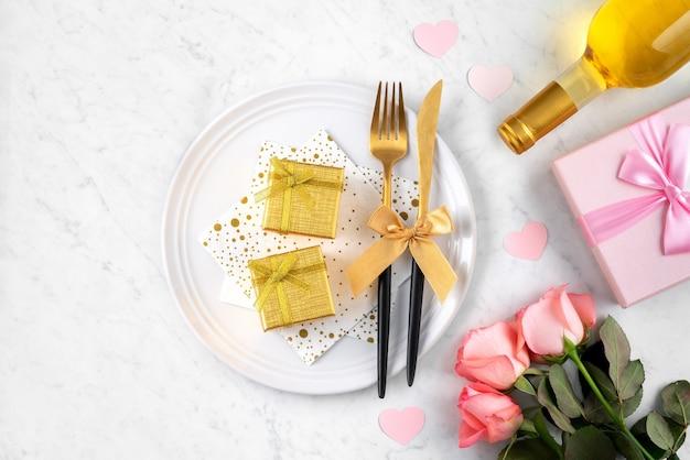 Белая тарелка с подарком и розовым цветком на мраморном белом фоне стола для специальной праздничной еды в день святого валентина.
