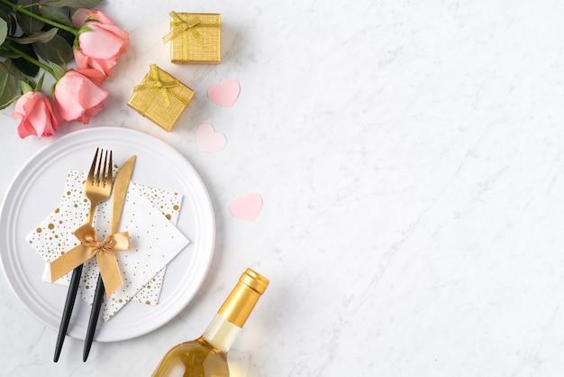 バレンタインデーの特別な休日のデートの食事のコンセプトのための大理石の白いテーブルの背景にギフトとピンクのバラの花と白いプレート。