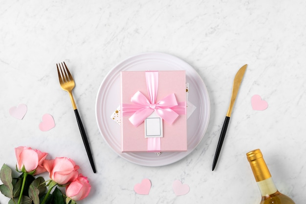 White plate with gift and pink rose flower on marble white table background for valentine's day special holiday dating meal concept.