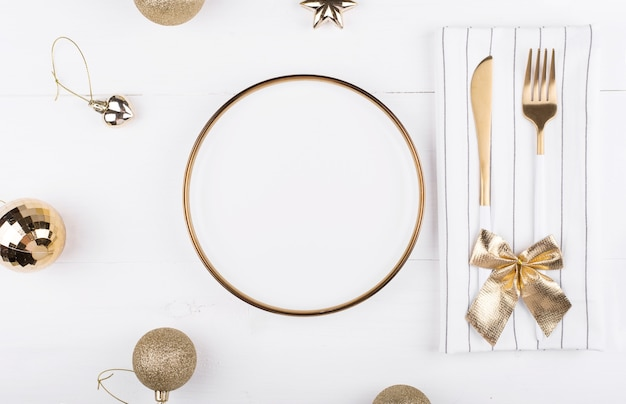 White plate with a gold border with christmas decorations around it, new year's menu, festive table setting.