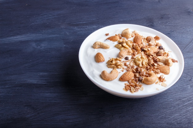 White plate with greek yogurt, granola, almond, cashew, walnuts  on black wooden.