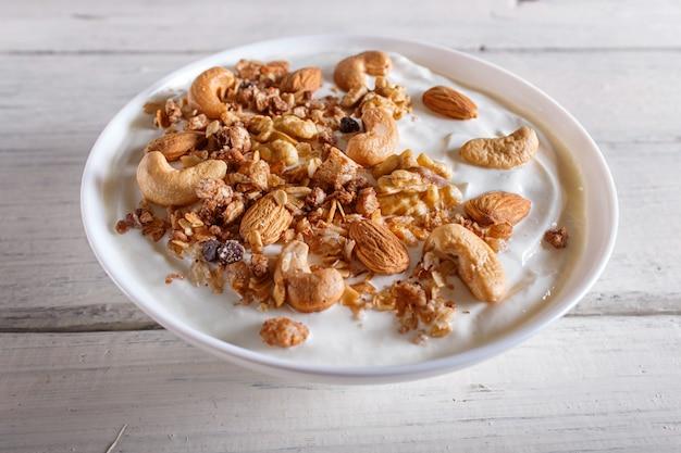 White plate with greek yogurt, granola, almond, cashew, walnuts on white wooden background.