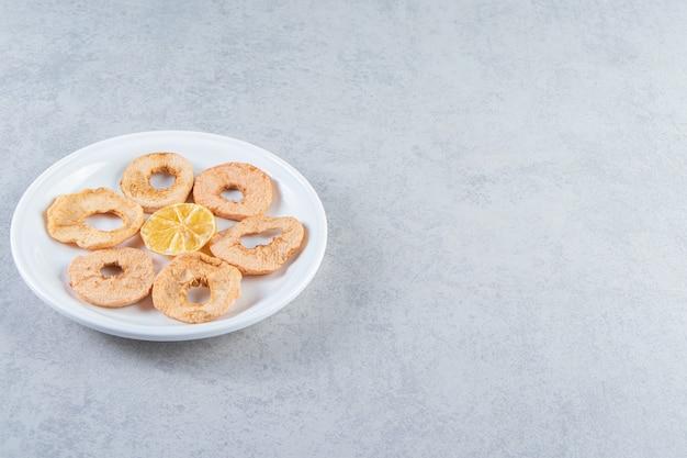 Un piatto bianco con frutta secca sana su sfondo marmo.