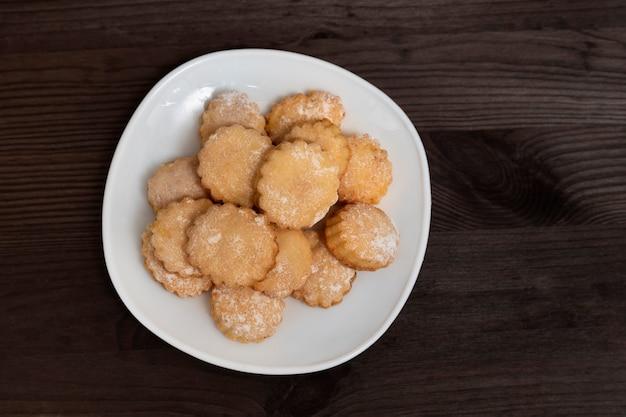 Белая тарелка с домашним песочным печеньем на деревянном столе. вид сверху. выпечка к чаю.