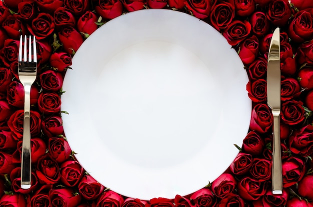 Белая тарелка с ножом и вилкой на фоне роз для обеда на годовщину или концепцию дня святого валентина.