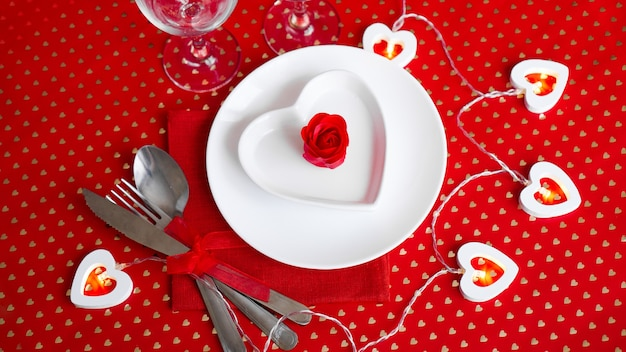 A white plate with a knife and fork on a bright red. heart shaped white plate. valentines day. the view from the top.