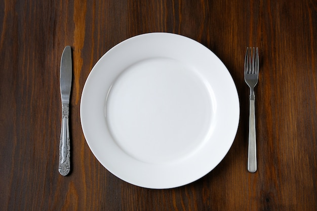 A white plate with a knife and fork on a wooden table