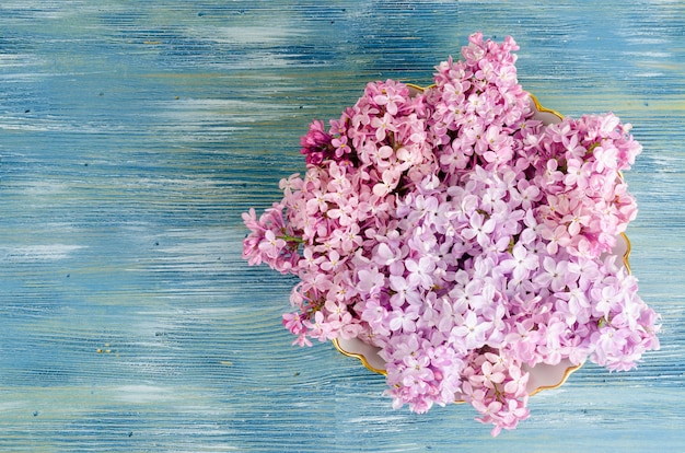 White plate with lilac flowers on table.
