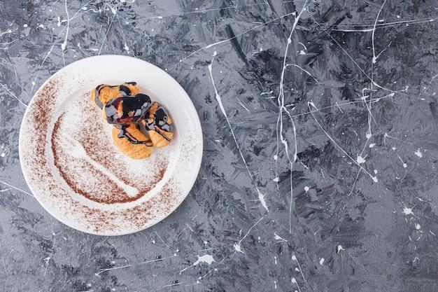 대리석 표면에 초콜릿 코팅이 된 미니 크로와상이있는 흰색 접시.