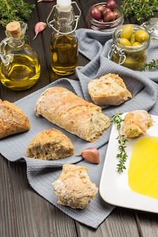 White plate with olive oil. jars of olives and bottles of oil, garlic and thyme sprigs. pieces of bread on gray napkin. top view.